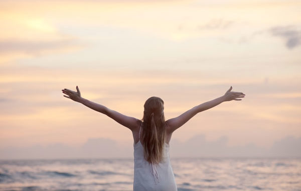 Una chica mira el atardecer mientras extiende sus brazos